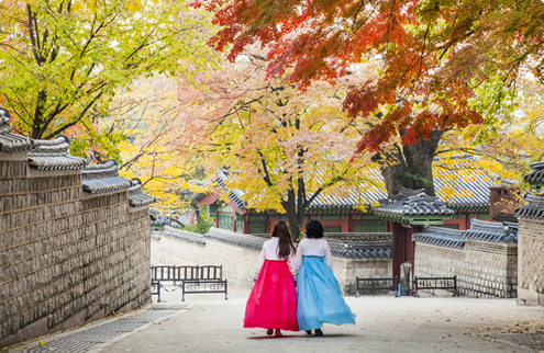 Two women dressed in hanboks walking along the walkway under the autumn leaves
