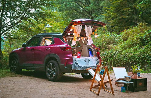 Car camping with the trunk open and lights decorating the outside and inside of the car and casual camping gear set up in front
