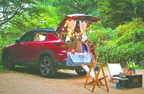 Красный внедорожник в парке с открытым багажником, в котором установлены декорации для кемпинга, и со столом и стульями расположенными на земле.