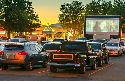 映画上映中のドライブインシアターで自動車が数台が並んでいるイメージ