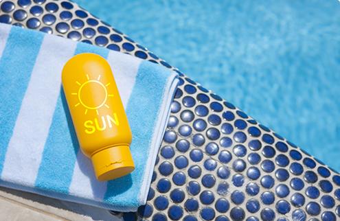 游泳池旁的毛巾與防曬乳