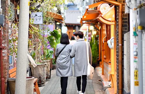 Пара гуляющая по узенькой улице в районе Иксон-дон, наслаждаясь свиданием