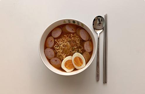 加入雞蛋與火腿的泡麵햄과 계란이 들어간 라면이 놓여있다