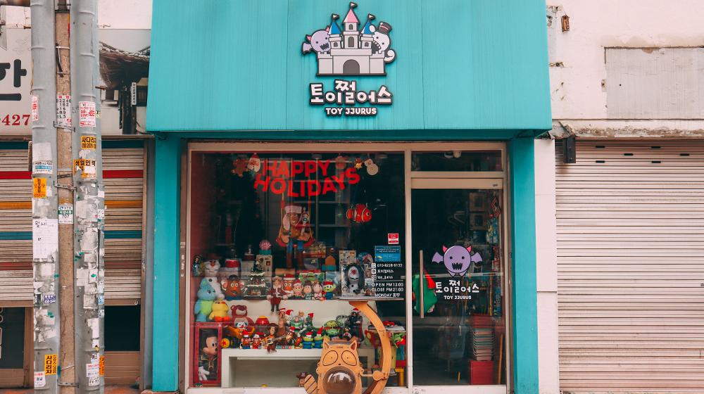 Вход в магазин Toy Jjurus с большим стеклянным окном и дверью через которые видно выставленные на показ игрушки