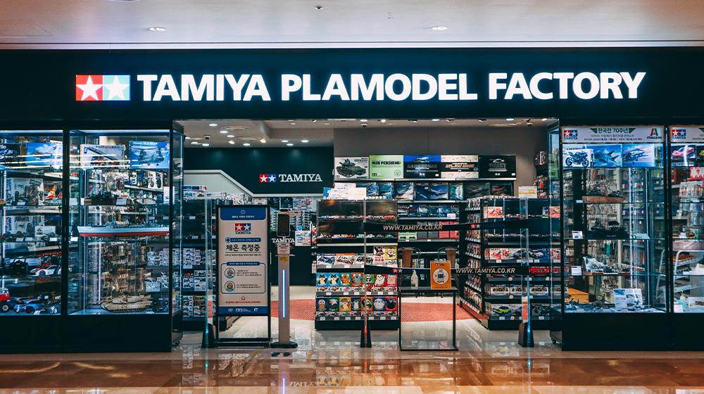 Вход в магазин Tamiya Plamodel Factory с большими стеклянными витринами и входом через которые видно выставленные на показ игрушки