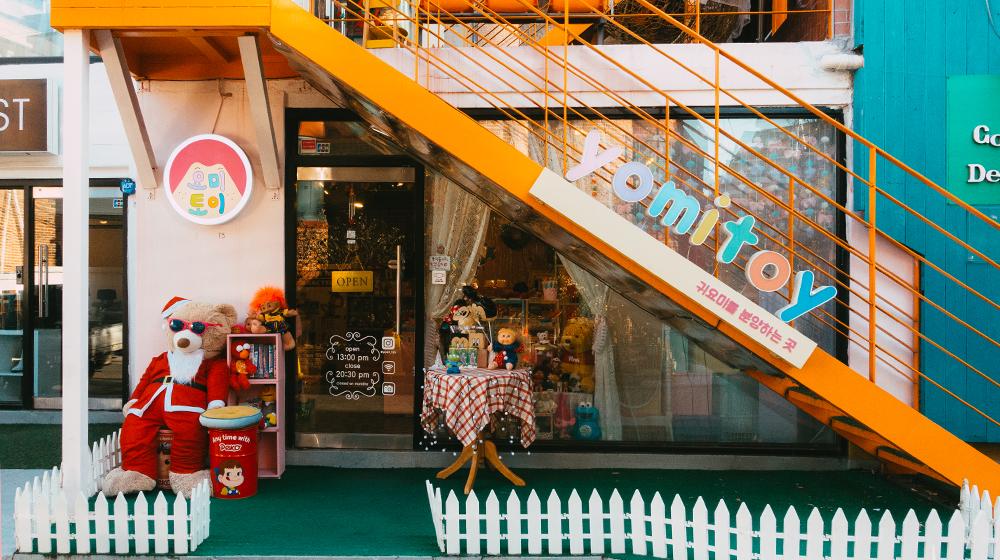 Вход в магазин Yomi Toy с милым маленьким белым забором, ведущей на второй этаж наружней оранжевой лестницей, и игрушками выставленными напоказ снаружи